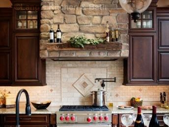 Natural materials define the style of this kitchen design including the stone hood and unique focal point backsplash.