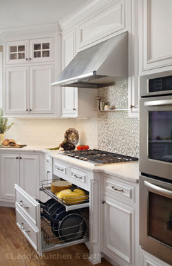 White kitchen design with pull-out drawer for storing pots and pans.