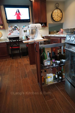 Kitchen design with specialized storage including a pull-out platform for a stand mixer.