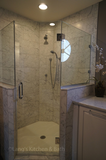 Bathroom design in Yardley, PA with Carrerra marble-tiled, angled shower
