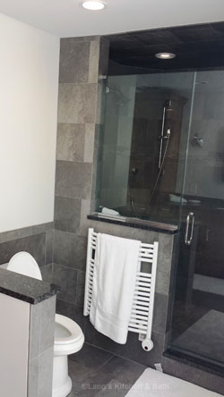 Bathroom design with a radiator style towel warmer next to the shower.