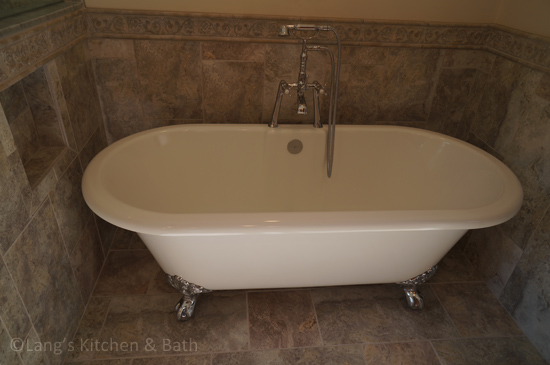 Bathroom design with freestanding tub with a built-in storage niche.