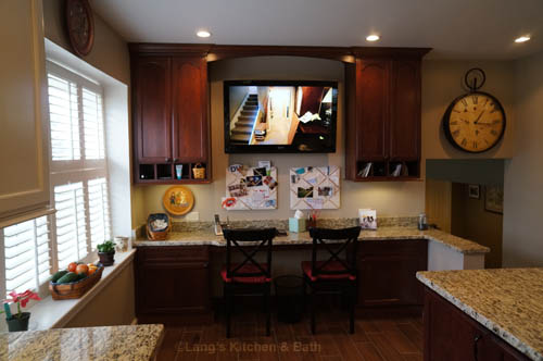 Kitchen design with a built in desk and wall-mounted flat screen television.