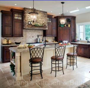 Kitchen design with a custom stone hood and furniture style kitchen cabinets.