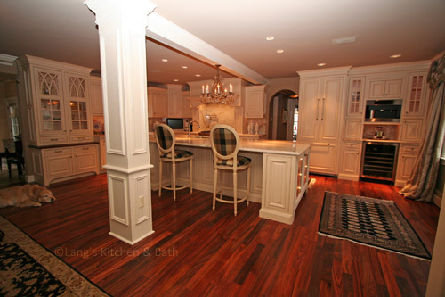 Open plan kitchen design with wood floors and architectural features.