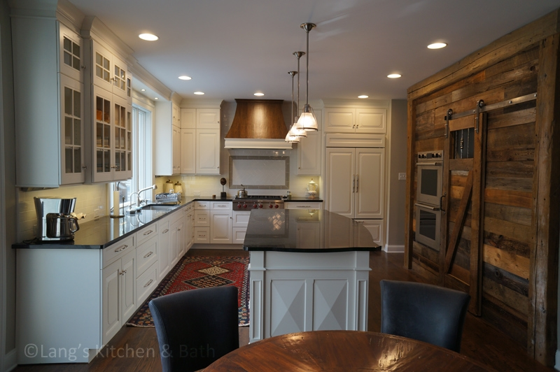 Traditional kitchen design with reclaimed barn wood and oak hood