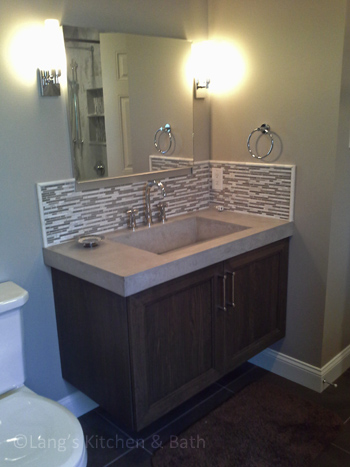Bathroom design with a mosaic tile backsplash.