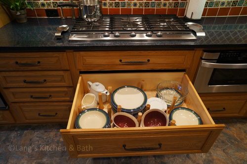 Kitchen design with crockery drawer with peg inserts.
