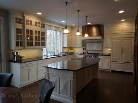 Kitchen design featuring white kitchen cabinets with custom oak range hood.