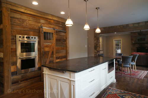 Kitchen design with white island cabinetry and reclaimed barn wood and sliding barn door.