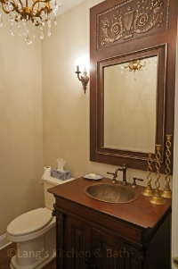 Bathroom design for a powder room with furniture style vanity and chandelier.