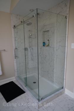 Bathroom design with a frameless glass shower enclosure.