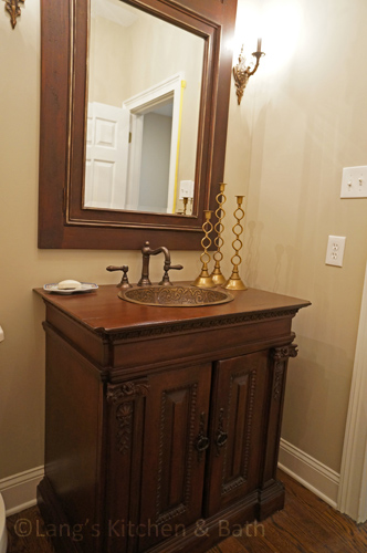 Powder room design with a furniture style vanity cabinet.