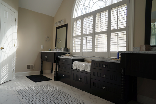 Traditional bathroom design with vanity cabinets around a central window.