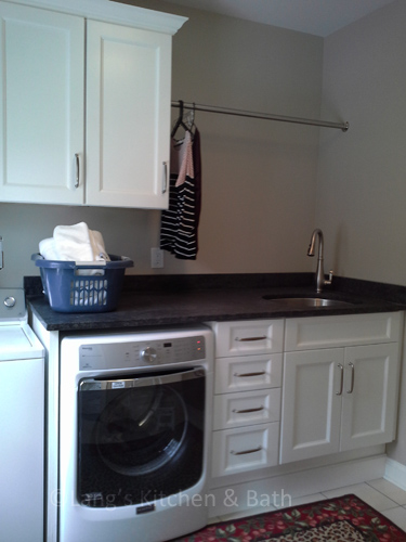 Laundry Room design with white cabinetry, sink, and bar for hanging clothes.