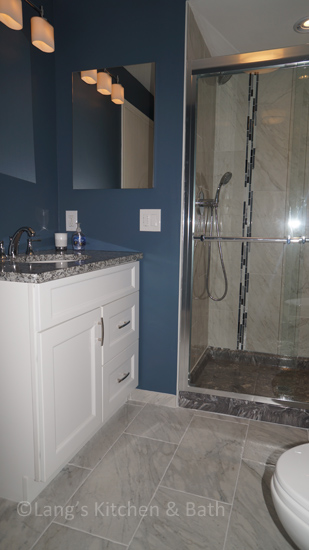 Bathroom design with single sink vanity and shower.