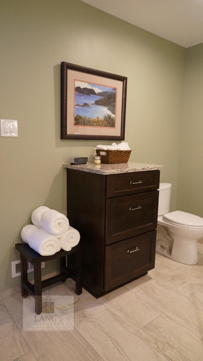 Master bath design with dark wood cabinetry