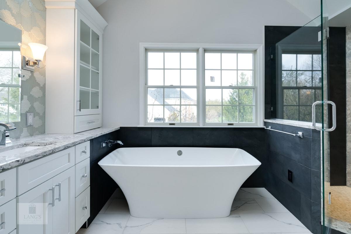 White freestanding bathtub with a black wall