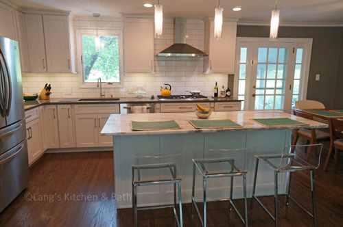 White kitchen design with stainless hood
