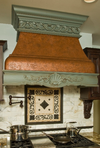 Traditional kitchen design with custom copper hood