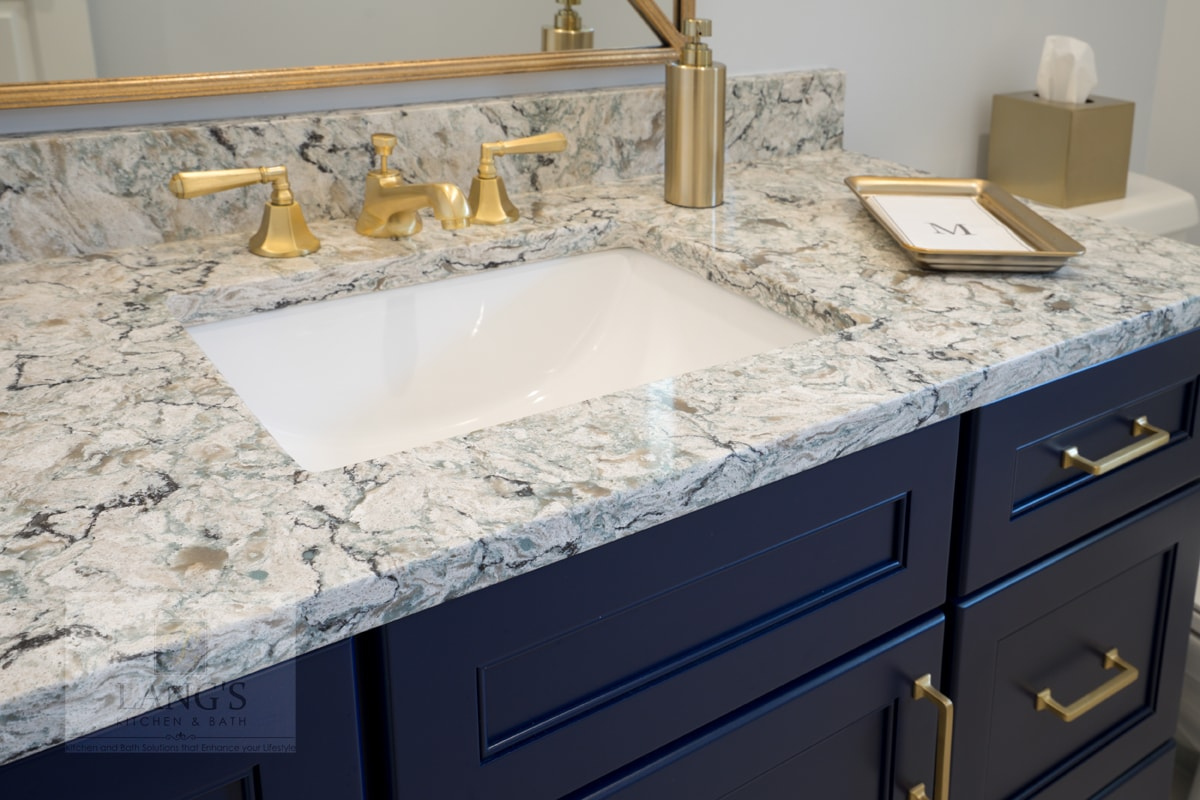 brass fixtures with blue vanity cabinet