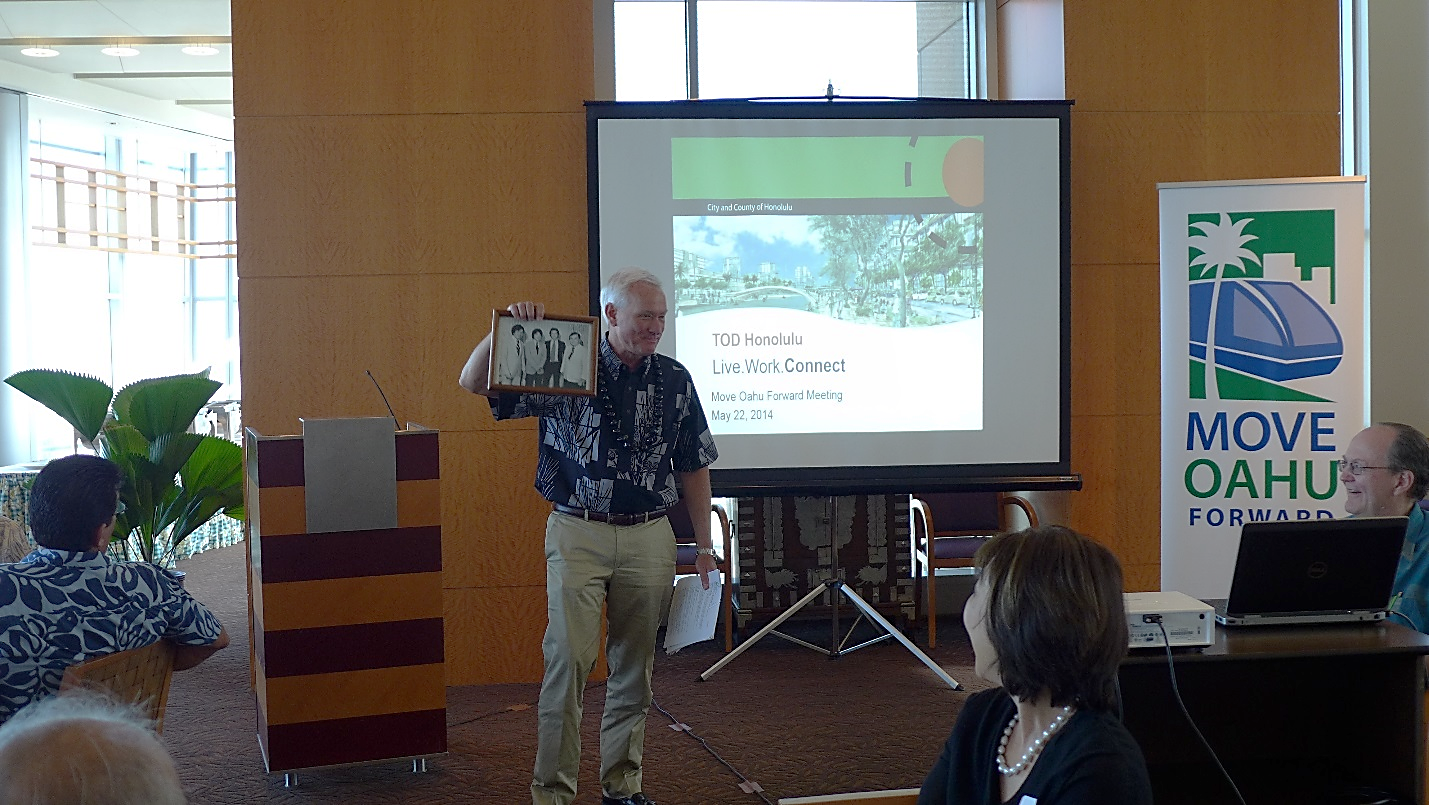 "Mayor Kirk Caldwell holds up a photo given to him by Move Oahu Forward executive director Jennifer Sabas of his ""younger days"" when he was in Washington D.C."