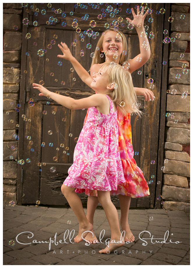 Portrait of girls dancing with bubbles on rustic door background by photographers Campbell and Salgado.