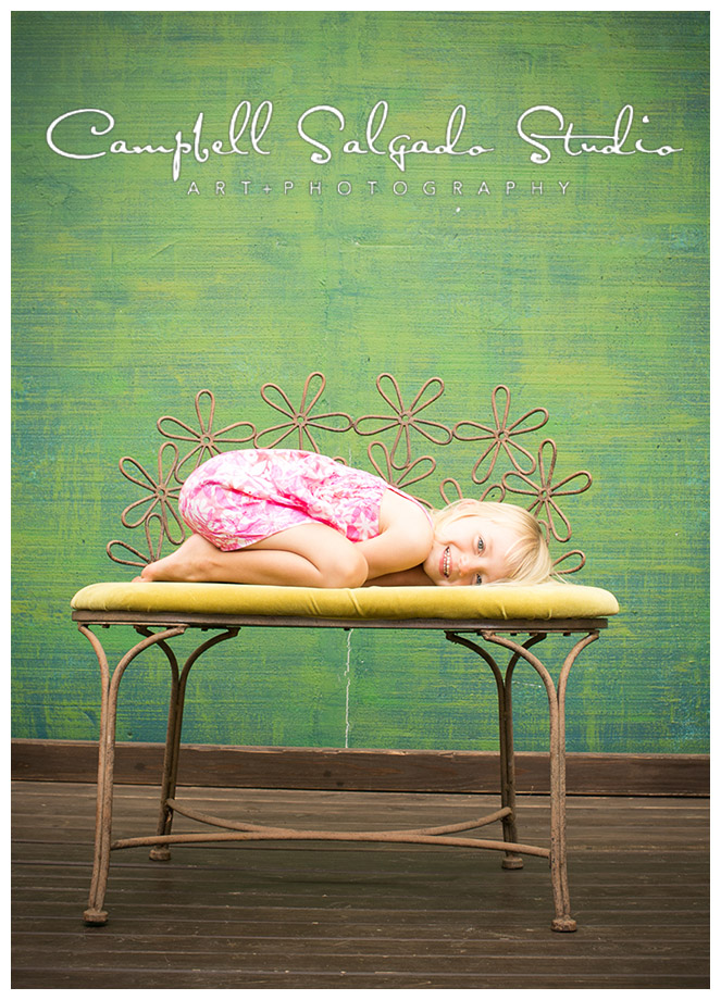 Portrait of little girl on bench on green background at Campbell Salgado Studio.