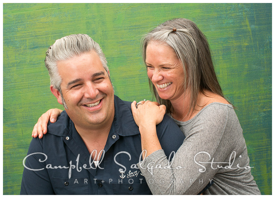 Portrait of couple on green background in Portland, Oregon by photographers Campbell and Salgado.