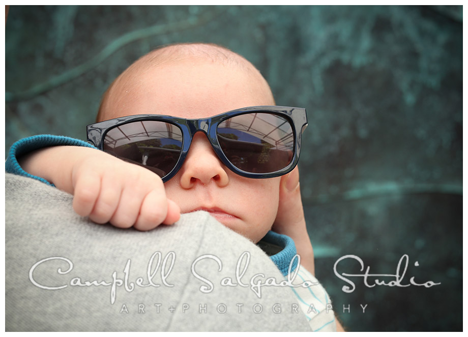 Portrait of baby in sunglasses on copper background at Campbell Salgado Studio.