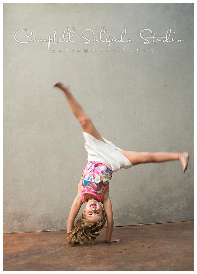 Portrait of girl doing cartwheel on grey background by Campbell Salgado Studio.