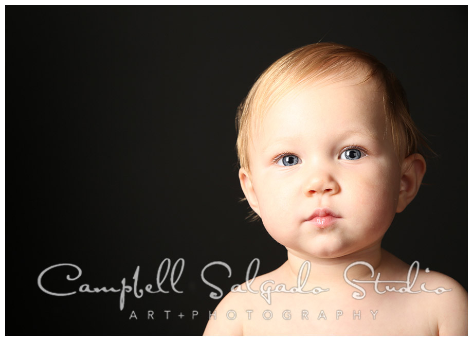 Portrait of baby girl on black background at Campbell Salgado Studio.