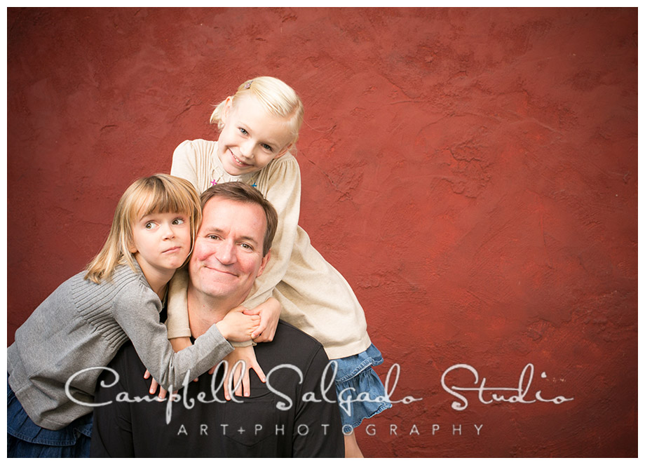 Portrait of dad and daughters on red background at Campbell Salgado Studio.