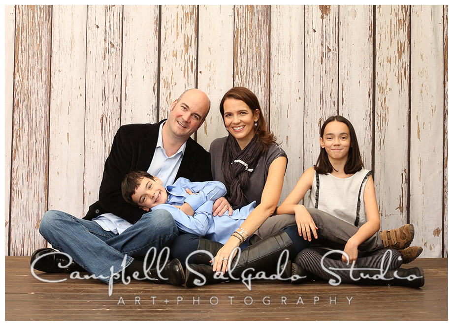 Portrait of family on wooden fence background by photographers Campbell and Salgado.