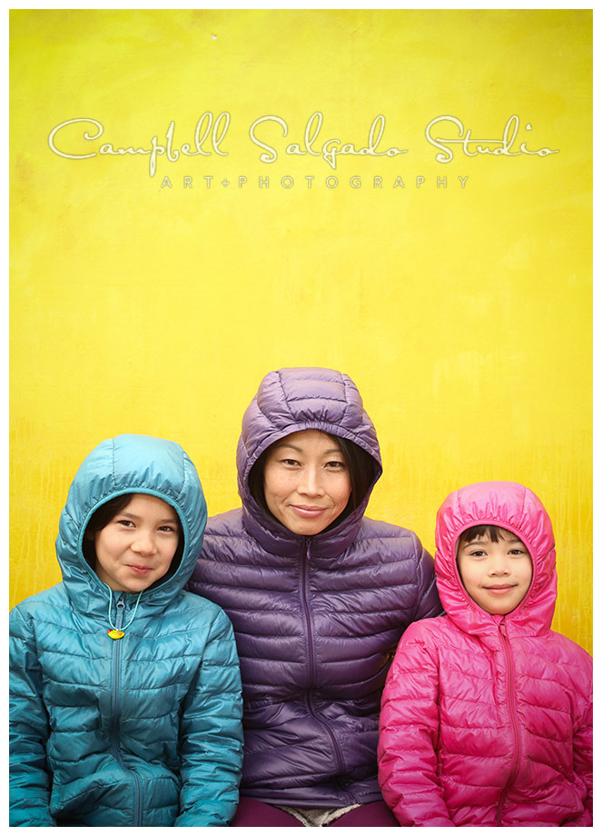 Portrait of mother and daughters on yellow background at Campbell Salgado Studio.