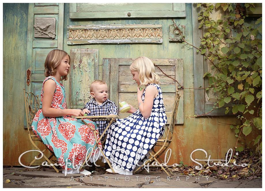 Portrait of kids having a tea party on vintage doors background at Campbell Salgado Studio.