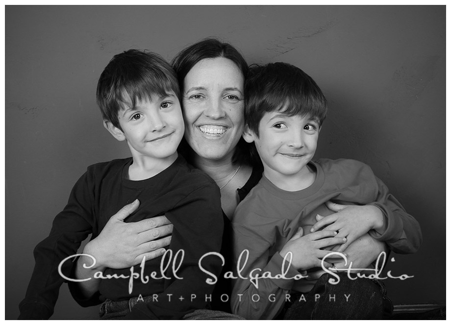 B&W portrait of mom and boys on grey background at Campbell Salgado Studio.