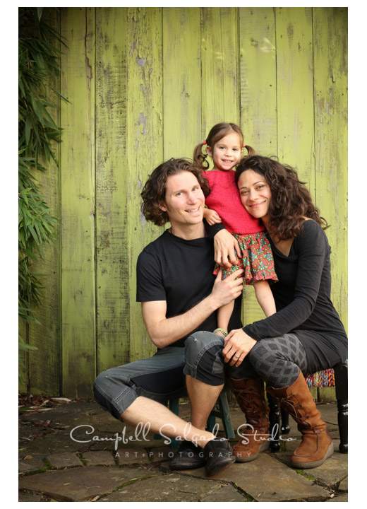 Portrait of family on green fence boards at Campbell Salgado Studio in Portland, Oregon.