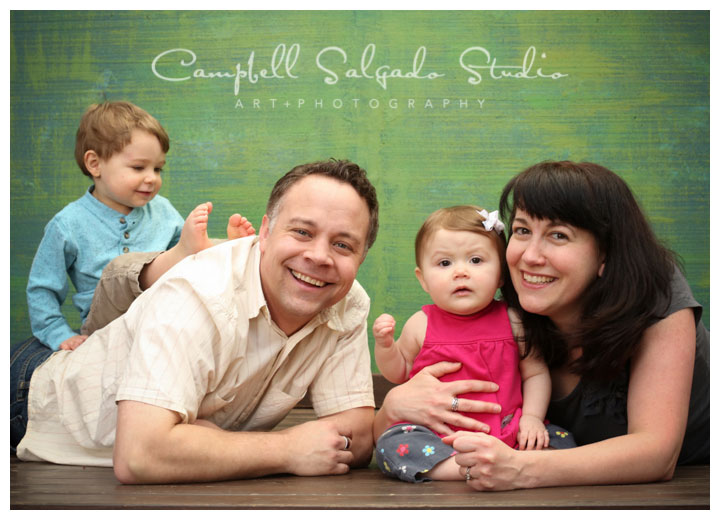 Portrait of family on green background by family photographers at Campbell Salgado Studio.