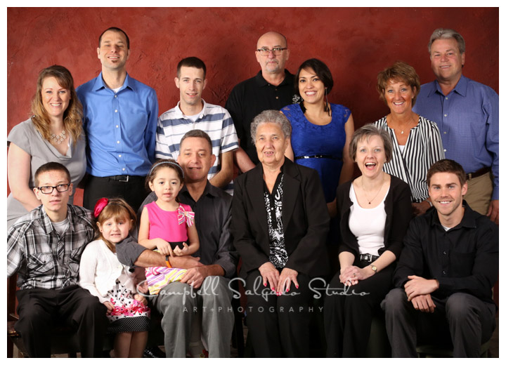 Portrait of extended family on red background in Portland, Oregon by Campbell Salgado Studio.