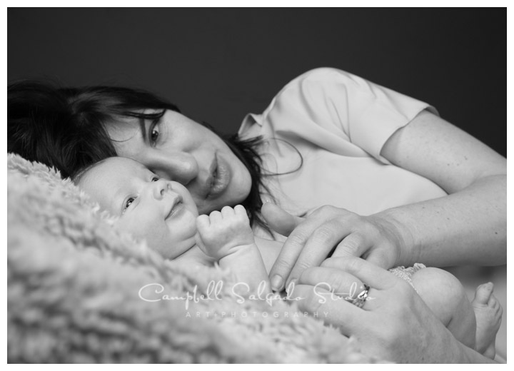 B&W portrait of mama and newborn baby girl on grey background at Campbell Salgado Studio.