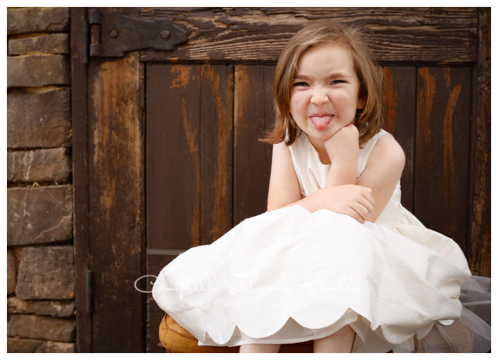 Portrait of child on rustic door background at Campbell Salgado Studio.