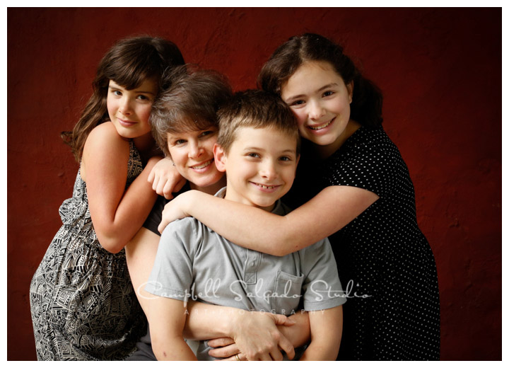 Portrait of family on red stucco background at Campbell Salgado Studio.