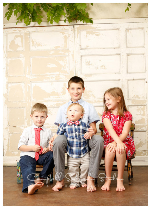 Portrait of kids on antique white doors background at Campbell Salgado Studio.