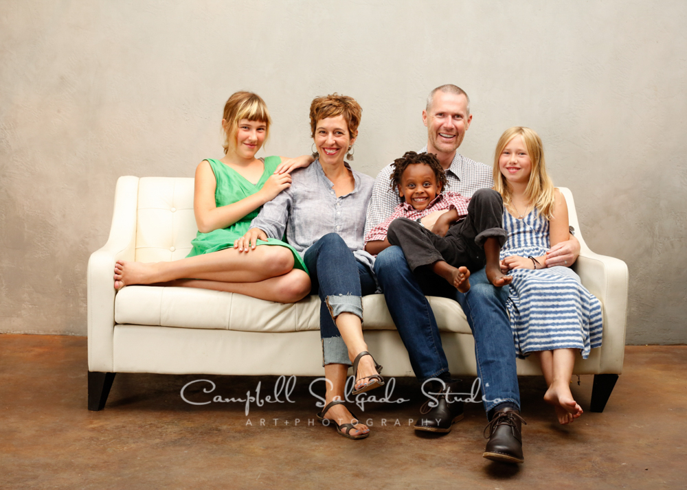 Family sitting on a couch for a portrait by family photographers at Campbell Salgado Studio, Portland, Oregon.