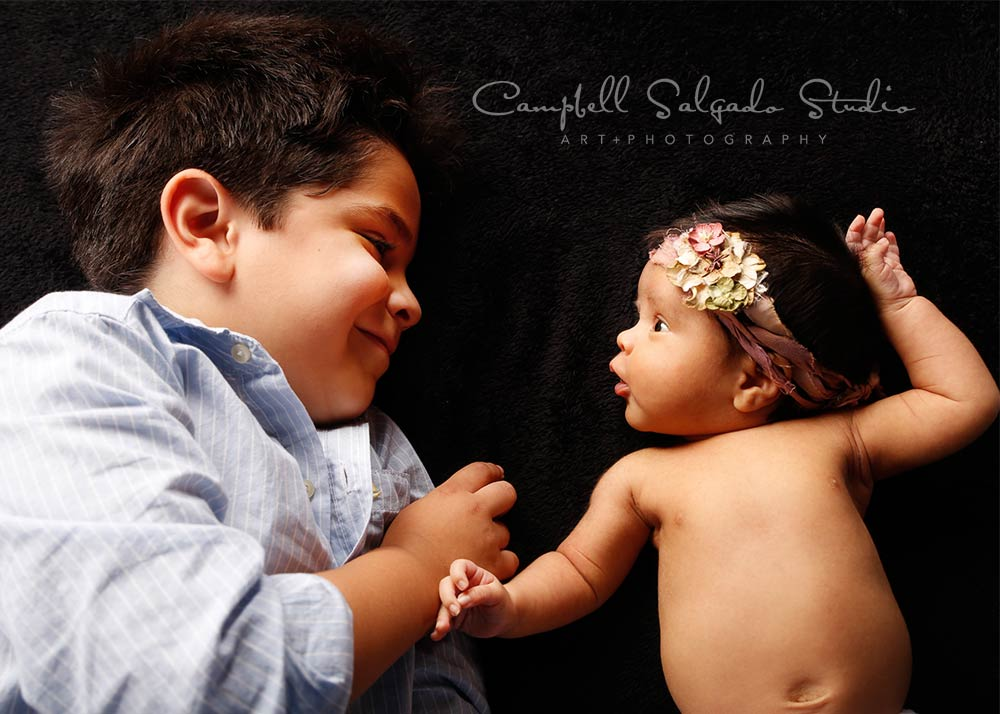 Newborn photography—5 year old boy smiling at one month old sister—by Portland, Oregon newborn photographers at Campbell Salgado Studio.