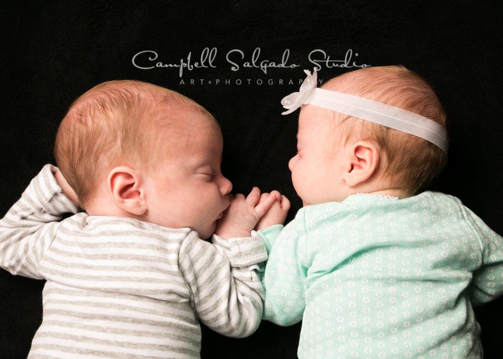 Portrait of twins on black background by newborn photographers at Campbell Salgado Studio, Portland, Oregon.