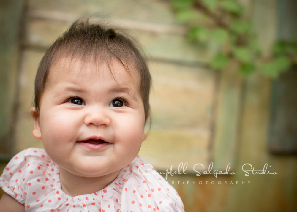 Portrait of baby girl on vintage green doors backgroundby family photographers at Campbell SalgadoStudio, Portland, Oregon.