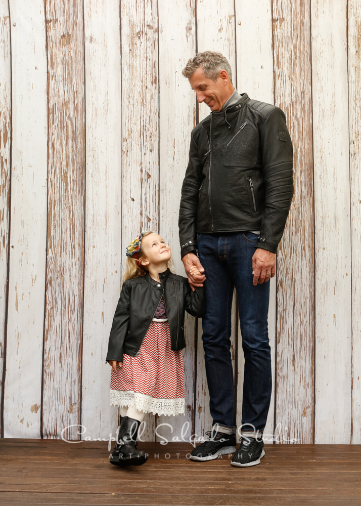 Portrait of father and daughter on white fence boards background by family photographers at Campbell Salgado Studio, Portland, Oregon.