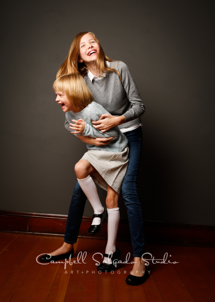 Portrait of sisters on grey background by family photographers at Campbell Salgado Studio, Portland, Oregon.